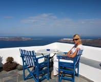 阳台美丽的坐的妇女 免版税图库摄影