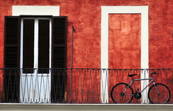 阳台自行车意大利红色墙壁 库存照片