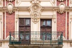 阳台,有在葡萄酒砖房子的门面的Windows的 库存照片