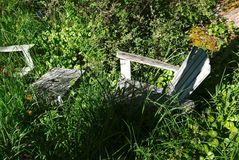 阴影和杂草在庭院掩藏两把绿色adirondack椅子 库存照片