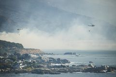 阵营咆哮,开普敦, 2017年10月13日-直升机战斗阵营猛烈的向西风扇动的海湾火 免版税库存图片