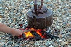 阵营在海滩的水壶火 库存图片