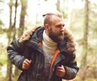 阵营,冒险,旅行和友谊概念 有远足在森林里的背包和胡子的人 库存图片