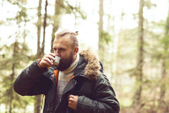 阵营,冒险,旅行和友谊概念 有远足在森林里的背包和胡子的人 免版税库存照片
