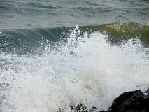 水滴阵雨由于海挥动碰撞在岩石 免版税图库摄影