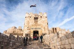 阿勒颇,叙利亚,访客不久之前退出阿勒颇城堡门在叙利亚内战结束时2010年开始  免版税库存图片