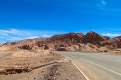 阿塔卡马沙漠干旱的风景和柏油路 免版税库存图片