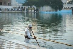 阿姆利则2月26日2018年,印度 老锡克教徒清洗湖附近的金黄寺庙 免版税库存照片