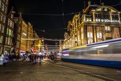 阿姆斯特丹市用不同的种类移动的路人运输&剪影的夜街道  免版税库存照片