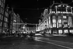 阿姆斯特丹市用不同的种类移动的路人运输&剪影的夜街道  免版税库存图片
