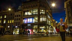 阿姆斯特丹市用不同的种类移动的路人运输&剪影的夜街道  库存照片