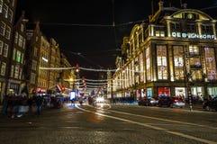 阿姆斯特丹市用不同的种类移动的路人运输&剪影的夜街道  库存图片