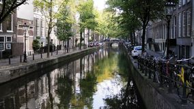 阿姆斯特丹市看法:清早,多云天,秋天-沿运河和自行车停放的汽车,树反射了  影视素材