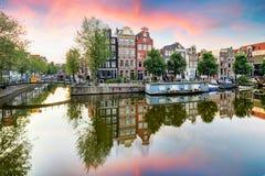 阿姆斯特丹日落反射的运河房子,荷兰 免版税图库摄影