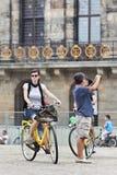 阿姆斯特丹水坝正方形的循环的游人 库存照片