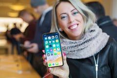 阿姆斯特丹荷兰 显示iPhone x的女孩在苹果计算机商店 图库摄影