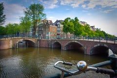 阿姆斯特丹,有花和自行车的在桥梁在运河,荷兰, 2017年7月08日 免版税库存图片