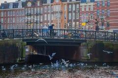 阿姆斯特丹,荷兰, 2018年3月, 10 :人们在阿姆斯特丹的历史部分的一座老石桥梁走,与 免版税库存图片