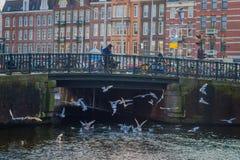 阿姆斯特丹,荷兰, 2018年3月, 10 :人们在阿姆斯特丹的历史部分的一座老石桥梁走,与 免版税图库摄影