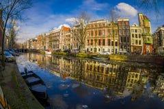 阿姆斯特丹,荷兰, 2018年3月, 10 :房子和小船室外看法在阿姆斯特丹运河 早晨照片颜色 免版税库存照片