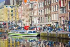 阿姆斯特丹,荷兰, 2018年3月, 10 :房子和小船美丽的景色在阿姆斯特丹运河,在荷兰样式与 免版税库存照片