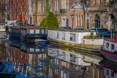 阿姆斯特丹,荷兰, 2018年3月, 10 :房子和小船美丽的景色在阿姆斯特丹运河,在荷兰样式与 免版税图库摄影
