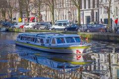 阿姆斯特丹,荷兰, 2018年3月, 10 :房子和小船美丽的景色在阿姆斯特丹运河,在荷兰样式与 免版税库存图片