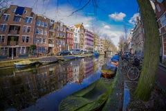 阿姆斯特丹,荷兰, 2018年3月, 10 :房子和小船美好的室外看法在阿姆斯特丹运河有冻河的 库存照片