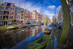 阿姆斯特丹,荷兰, 2018年3月, 10 :房子和小船美好的室外看法在阿姆斯特丹运河有冻河的 免版税库存图片