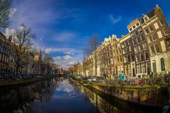 阿姆斯特丹,荷兰, 2018年3月, 10 :房子和小船美好的室外看法在阿姆斯特丹运河 早晨照片  免版税库存照片