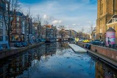 阿姆斯特丹,荷兰, 2018年3月, 10 :有些汽车出色的意见在接近许多小船的街道停放了在 图库摄影