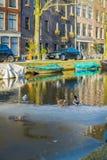 阿姆斯特丹,荷兰, 2018年3月, 10 :有些汽车室外看法停放了接近在阿姆斯特丹运河的小船  免版税库存图片