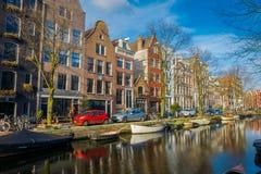 阿姆斯特丹,荷兰, 2018年3月, 10 :有些汽车室外看法在接近的街道停放了在运河的小船  免版税库存照片