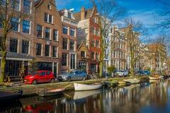 阿姆斯特丹,荷兰, 2018年3月, 10 :有些汽车室外看法在接近的街道停放了在运河的小船  图库摄影