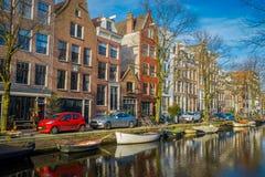 阿姆斯特丹,荷兰, 2018年3月, 10 :有些汽车室外看法在接近的街道停放了在运河的小船  库存照片