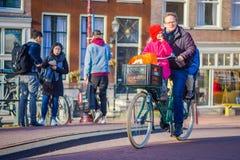 阿姆斯特丹,荷兰, 2018年3月, 10 :未认出的在历史部分的人民乘坐的自行车在阿姆斯特丹 免版税库存照片