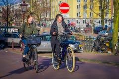 阿姆斯特丹,荷兰, 2018年3月, 10 :未认出的在历史部分的人民乘坐的自行车在阿姆斯特丹 库存照片