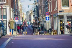 阿姆斯特丹,荷兰, 2018年3月, 10 :未认出的在历史部分的人民乘坐的自行车在阿姆斯特丹 免版税库存图片