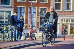 阿姆斯特丹,荷兰, 2018年3月, 10 :未认出的妇女骑马在历史部分骑自行车在阿姆斯特丹 免版税库存图片