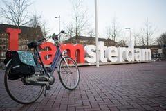 阿姆斯特丹,荷兰- 2018年2月,第17:我在巴克罕议会中心前面被安置的阿姆斯特丹标志和停放的自行车  库存照片