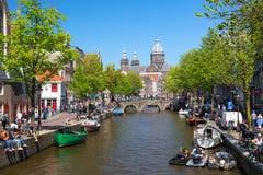 阿姆斯特丹,荷兰- 2018年5月:圣尼古拉斯教会有老镇运河的在春天好日子期间在阿姆斯特丹,荷兰 库存照片