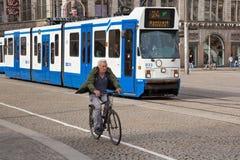 阿姆斯特丹,荷兰- 2017年6月25日:一辆自行车的年长人在一辆通过的BN建筑Ferroviaires电车Serie 12G旁边 免版税库存图片