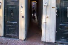 阿姆斯特丹,荷兰- 2014年6月10日:在街道的狭窄的段落在阿姆斯特丹 免版税库存照片