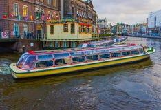 阿姆斯特丹,荷兰- 2017年12月14日:在阿姆斯特丹运河的巡航小船  图库摄影