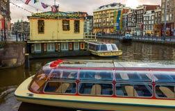 阿姆斯特丹,荷兰- 2017年12月14日:在阿姆斯特丹运河的巡航小船  免版税库存照片