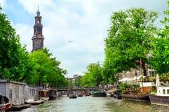 阿姆斯特丹,荷兰- 2010年6月10日:Westerkerk钟楼和运河视图在阿姆斯特丹,运河城市 免版税库存照片