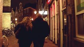 阿姆斯特丹,荷兰- 2017年12月28日 在晚上结合走沿狭窄的街道 库存照片