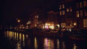 阿姆斯特丹,荷兰- 2017年12月27日 拥挤城市运河堤防和桥梁在晚上 库存图片