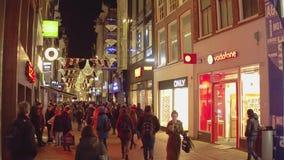 阿姆斯特丹,荷兰- 2017年12月28日 拥挤街道和被点燃的店面在晚上 库存照片
