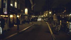 阿姆斯特丹,荷兰- 2017年12月26日 沿城市运河堤防走在晚上 免版税库存图片